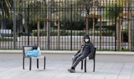 امرأة تجلس وحيدة مرتدية كمامة في حديقة عامة خالية من الناس في مدينة نيس الفرنسية